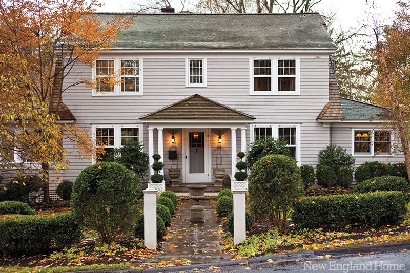 Trimmed hedges and topiary complement the dutch colonial for New england colonial house