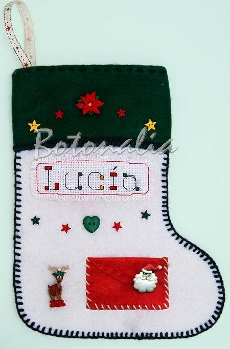 Bota navideña realizada den fieltro con botones decorativos de tema también navideño. Lleva un reno divertido, una cabeza de papa noel encima de un sobre de aplicación, un corazón y varias estrellas, todos botones. El nombre está bordado a punto de cruz. En la parte superior lleva un botón en forma de flor de pascua y más estrellitas. En el blog de Botonalia.com
