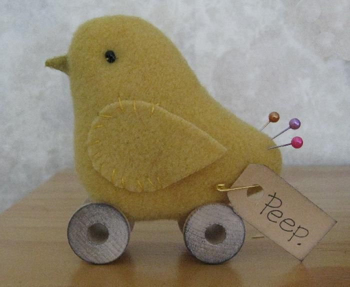 Baby chick make-do [pin cushion] on spool wheels. 100% wool, stick pin tail feathers, glass bead eyes and thread spool wheels. {Prim Penny via iHanna}    9.99 USD