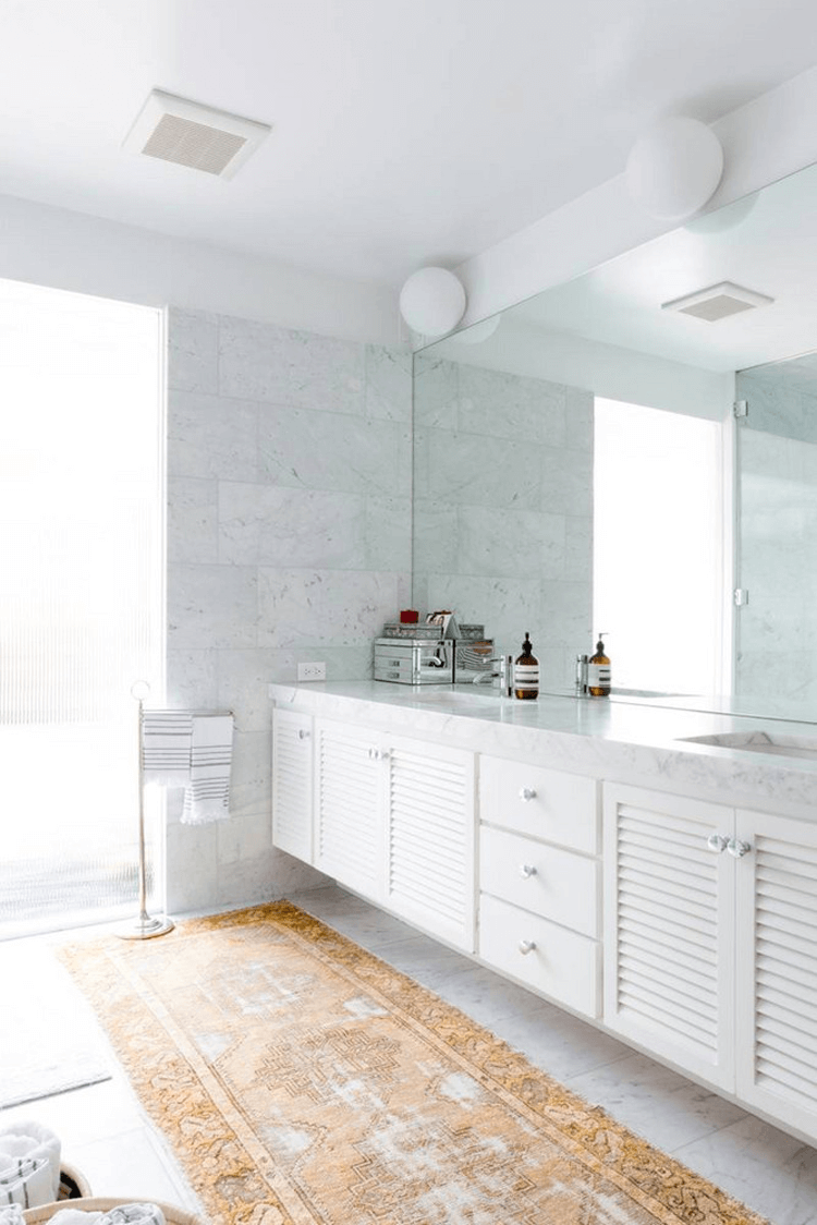A MODERN BATHROOM WITH WHITE MARBLE TILE AND VINTAGE RUG | Marble tiles