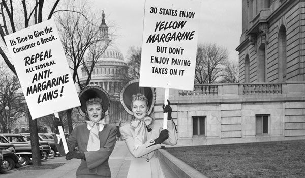 Mrs. J.C. Alicoate (L) of Miami, and Mrs. Arthur Hebb, Jr. of Baltimore, add their bit towards the fight for repeal of the tax on oleomargarine. They parade with their signs near the Capitol in 1949. (Bettmann / Contributor/Getty Images)