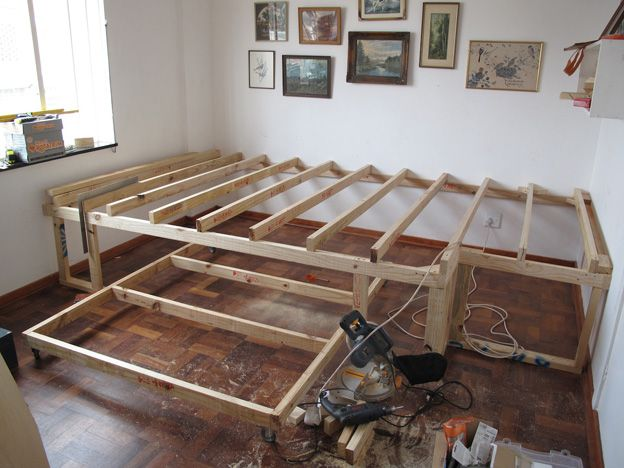 This guy combined two rooms into one by building a roll-away bed under a  stage, used for an office. You could even put two beds under the stage.