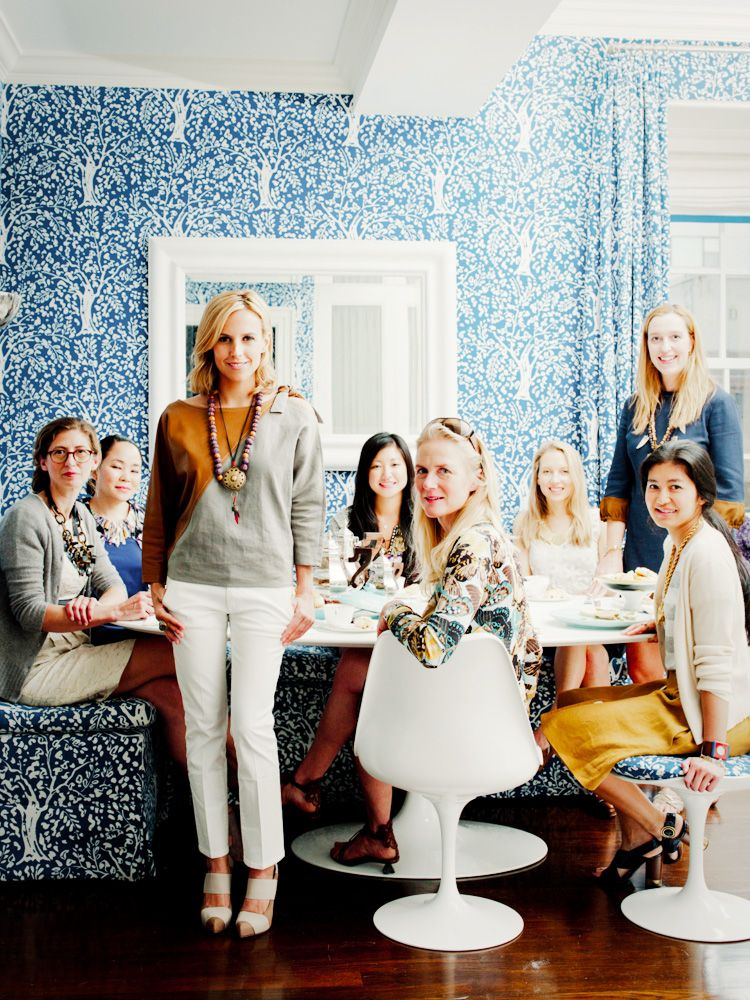 Tory Burch at a lunch meeting in a room with bright blue patterned walls and chairs