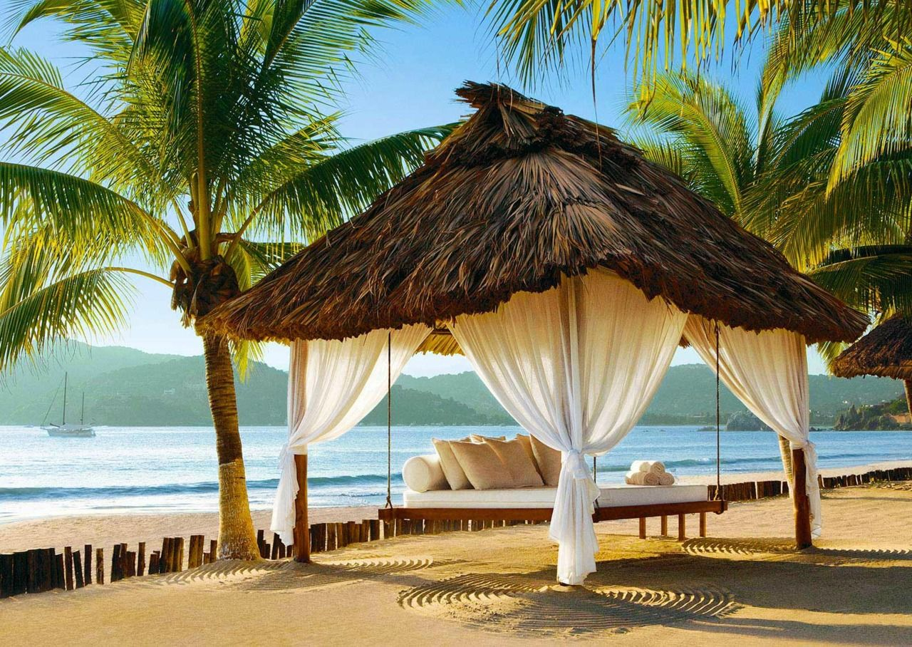 White Thatched Roofed Beach Cabana Bed Under Palm Trees By The