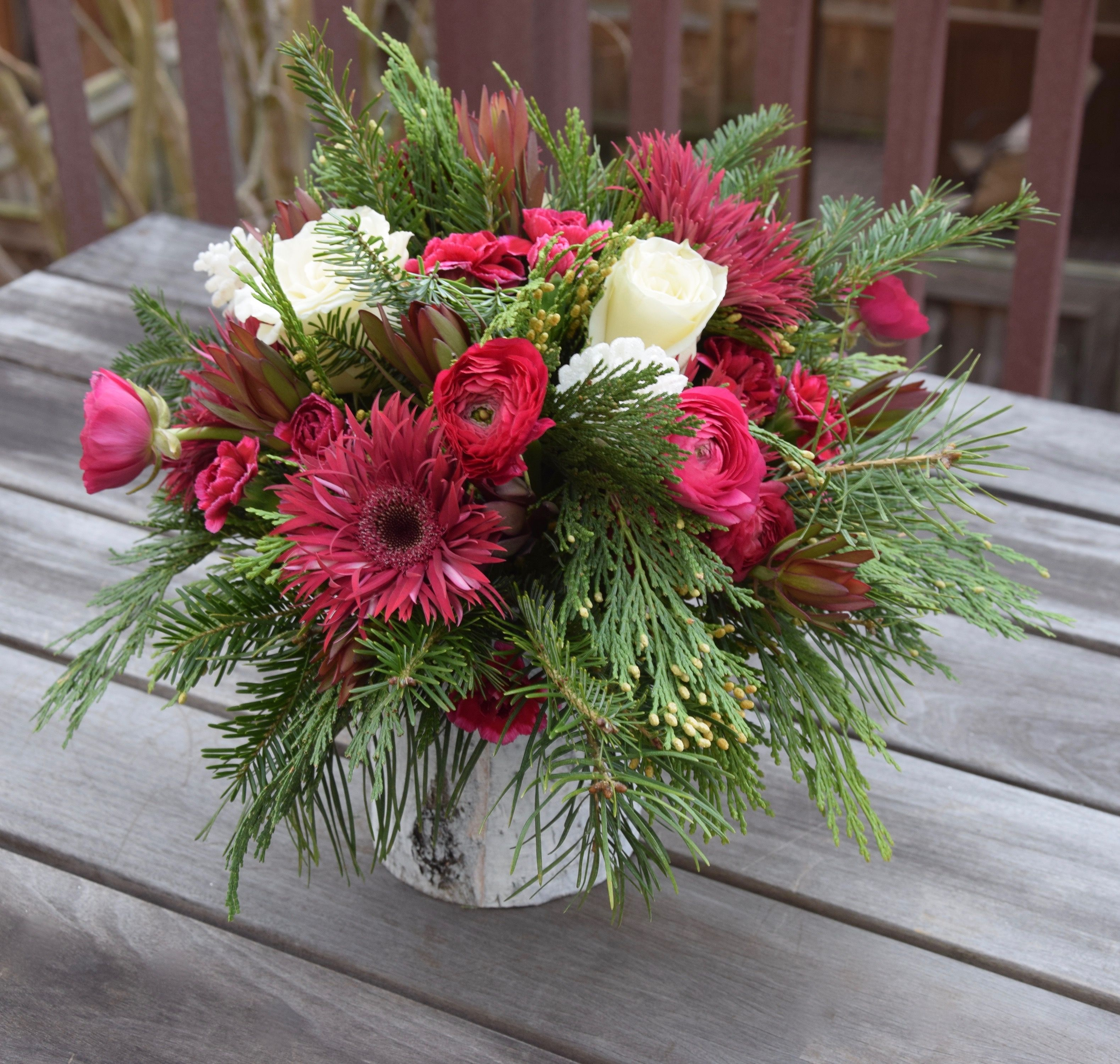 Holiday flower arrangement with winter greens, gerber daisies and ...