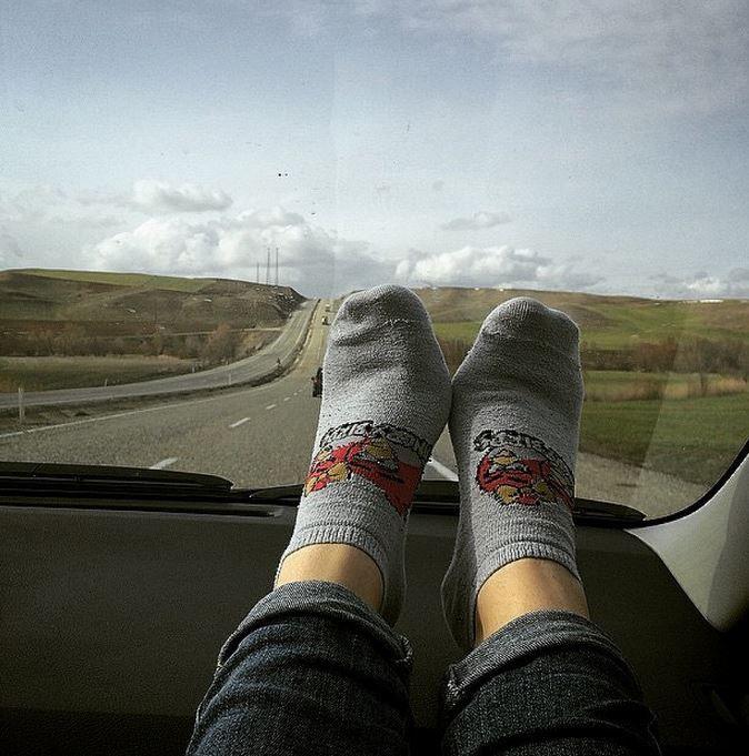 socked feet on the dashboard