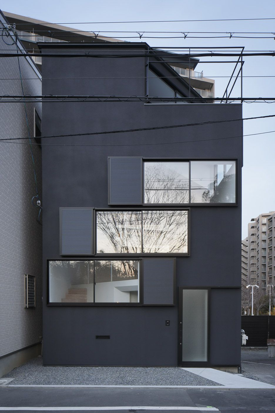 The long horizontal windows of this Osaka home frame different views of the nearby Yodo River.