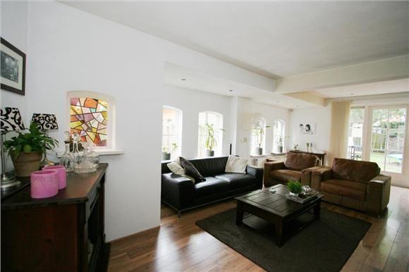 Ruime l vormige woonkamer voorzien van mooie laminaat vloer met