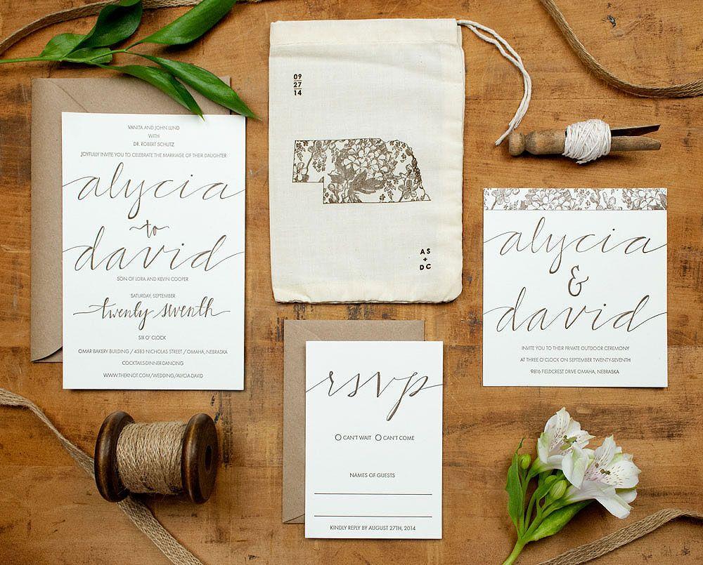 Rustic letterpress wedding invitation placed in printed muslin bag