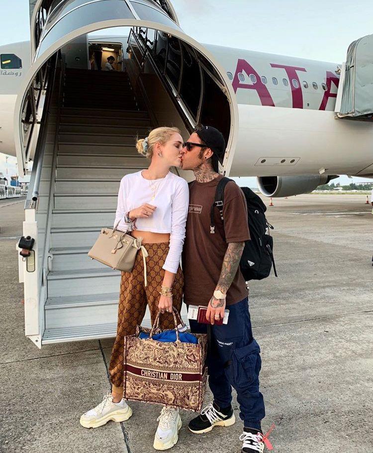 Un bacio e poi si vola Chiara e Fedez in un appassionato bacio poco prima di imbarcarsi su questo aereo La famosa influencer indossa una tuta di Gucci e una tshirt bianca...