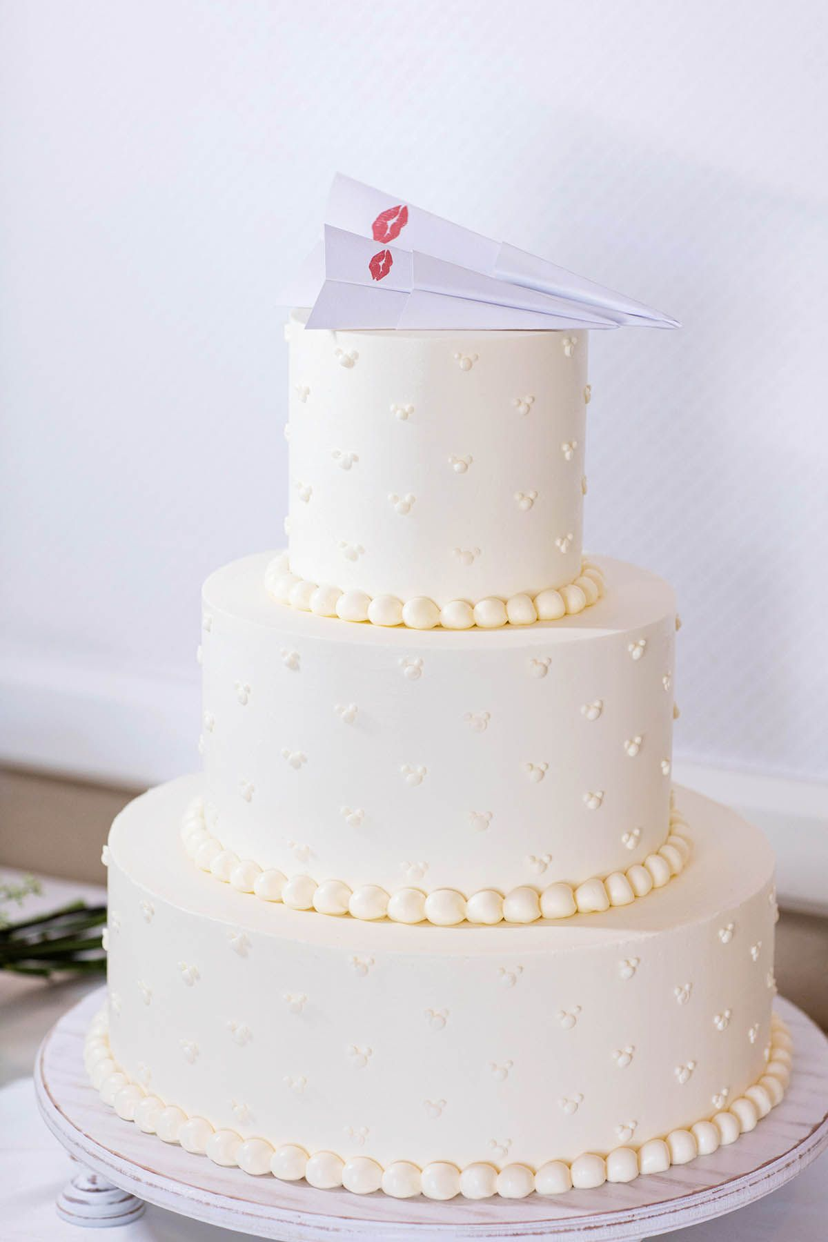 A simple white cake featuring a Paperman themed paper airplane ...