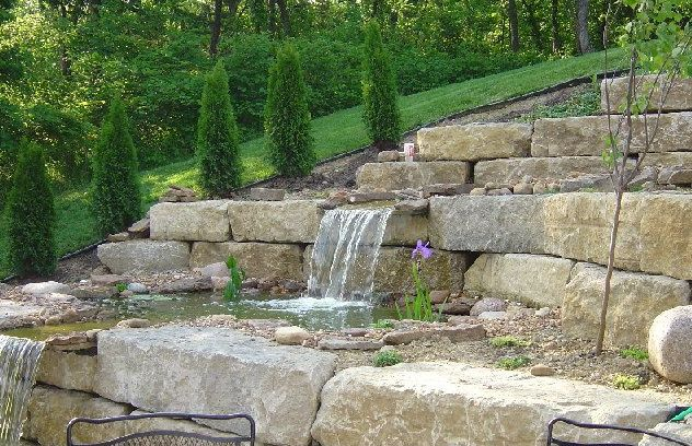 Large block stones retaining the slope plus a water for Cinder block pond ideas