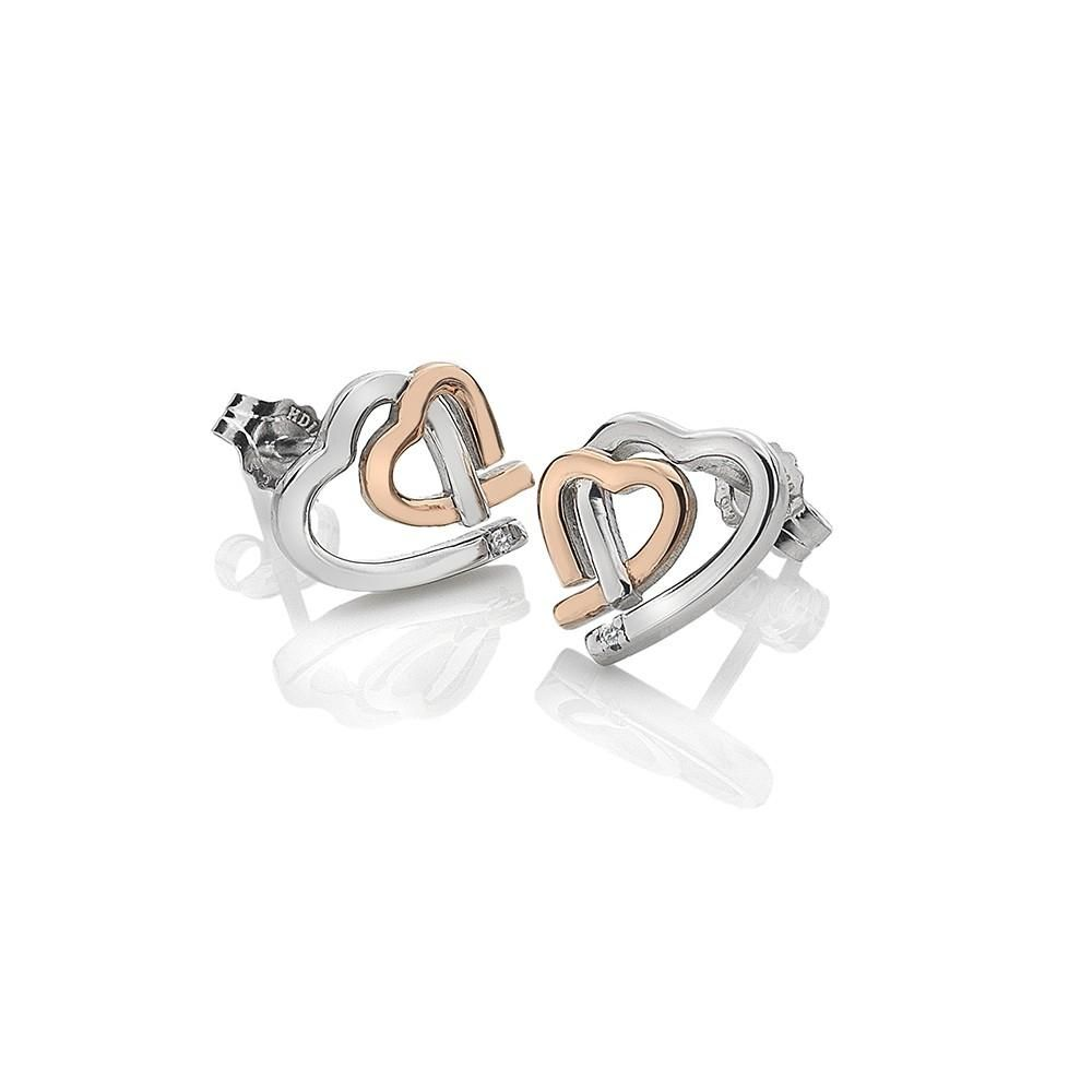 Sterling Silver Heart Studs Amore makes the world go round, wrap up your love with Amore Heart Studs. Smaller heart is plated with rose gold, interlinked to show true eternal love. The earrings are complete with a real diamond in each ear. T Rhodium and Rose Gold Plating 2 Diamonds: 0.01cttw Width: 11mm Height: 11mm Style#: B.hd0064 YOU MAY ALSO LIKE