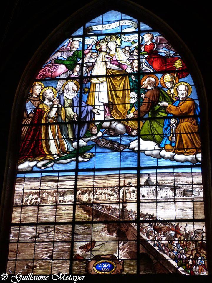 Une des grandes verrières de Saint-Saturnin de Blois. Il s'agit d'un ex-voto réalisé après la crue de la Loire du 29 septembre 1866. L'église est représentée à droite.