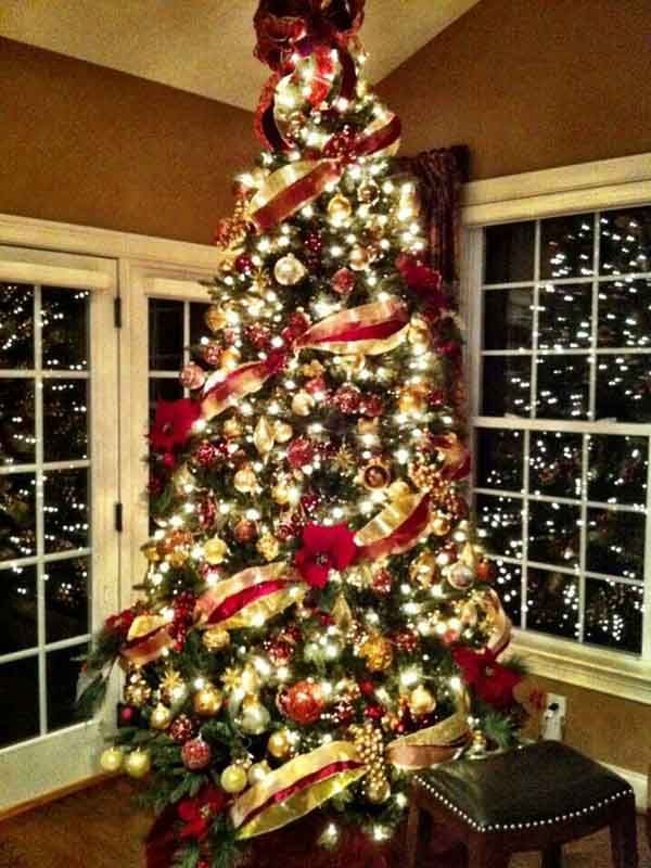 perfect balance is achieved by wrapping the ribbon at an angle around the tree and gathering the ribbon with poinsettias at an opposite angle around the