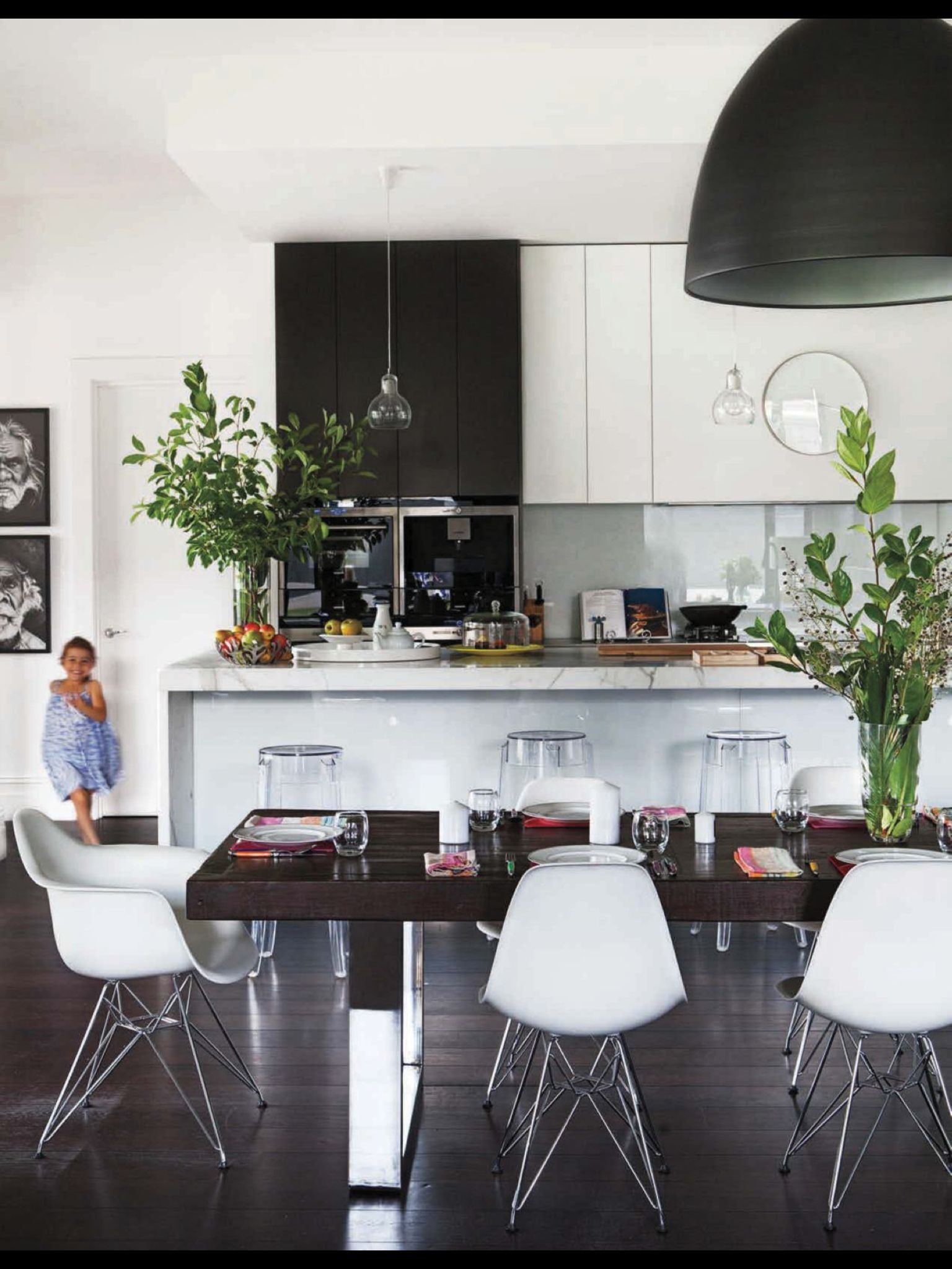 Black And White Kitchen With Glass Pendants Over Island