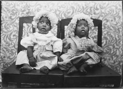 Seydou Keita   Twins in European dress   1952-1955 (taken) 1999 (print)       Gelatin silver print   15 1/4 x 21 1/4 in (38.7 x 54 cm)       Phillips de Pury - New York   Courtesy of Phillips De Pury - NY (31 Jan 2008, Lot 72)          LL/27361       Signed, dated '1999' and annotated in ink in the margin.