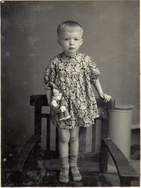 Vintage photo of a dainty little girl with a boyish haircut holding her small clown doll.