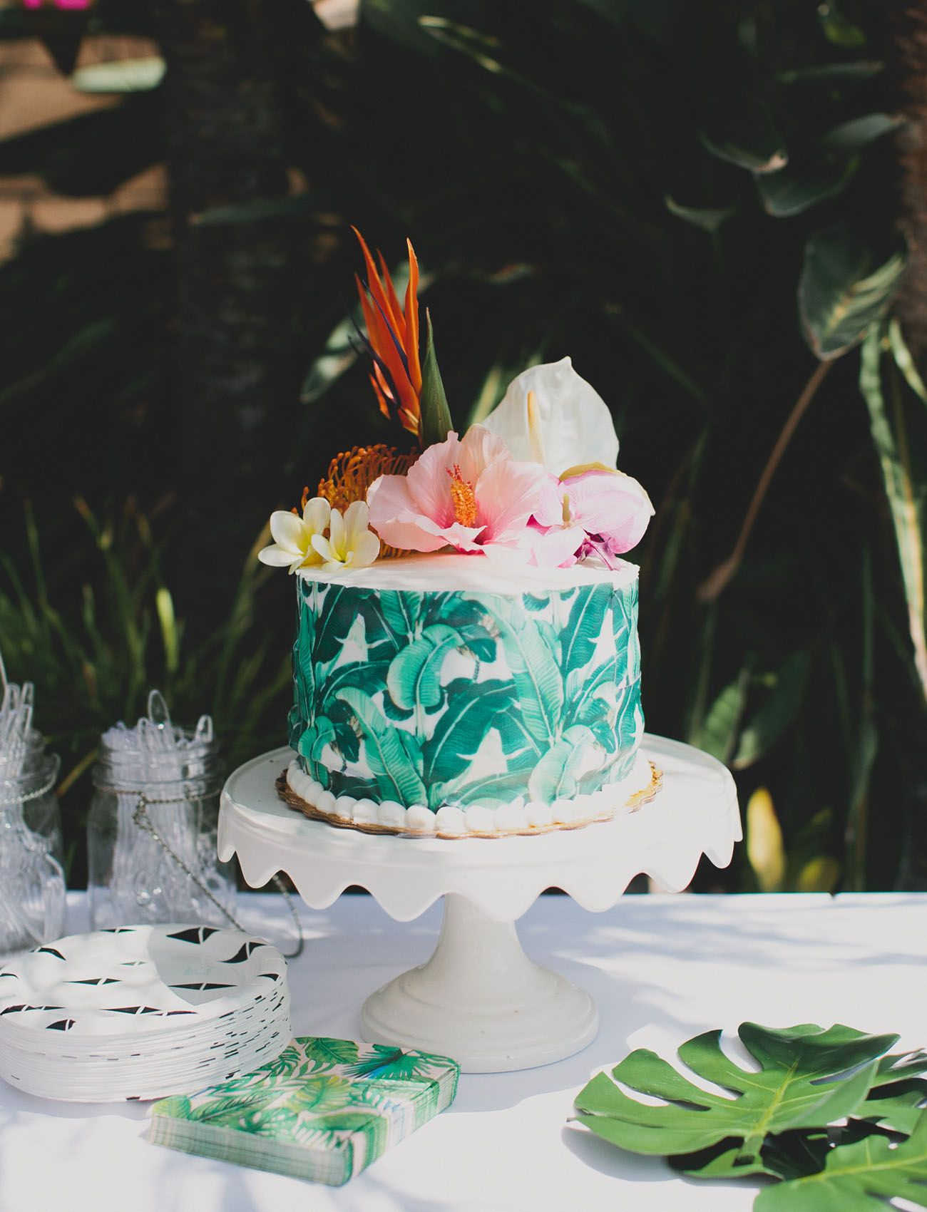 banana leaf wrapped cake paired with hibiscus bird of paradise and monstera leaves