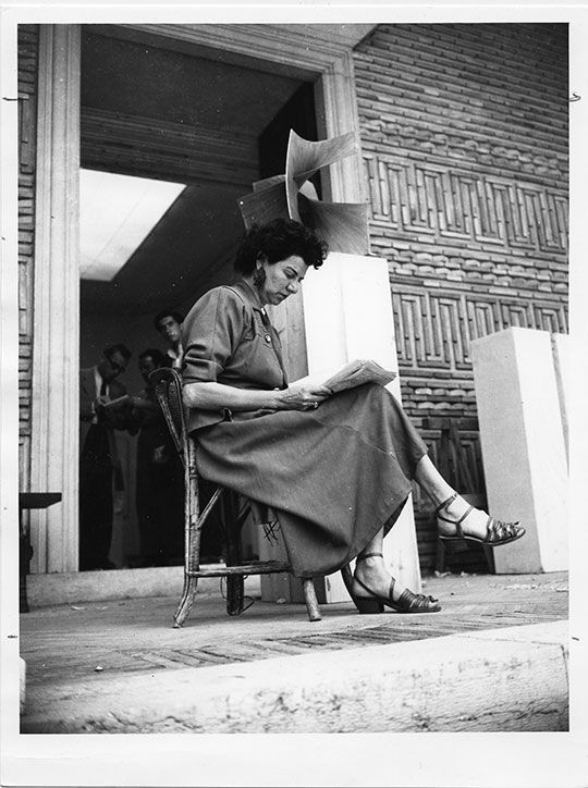 Peggy Guggenheim, pictured here at age 50, seated in front of the Greek Pavillion in 1948 at the 24th Venice Biennale, where she exhibited her collection.