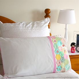 Make a pretty pillowcase for your guest room by stitching hexies to the front of the pillowcase.