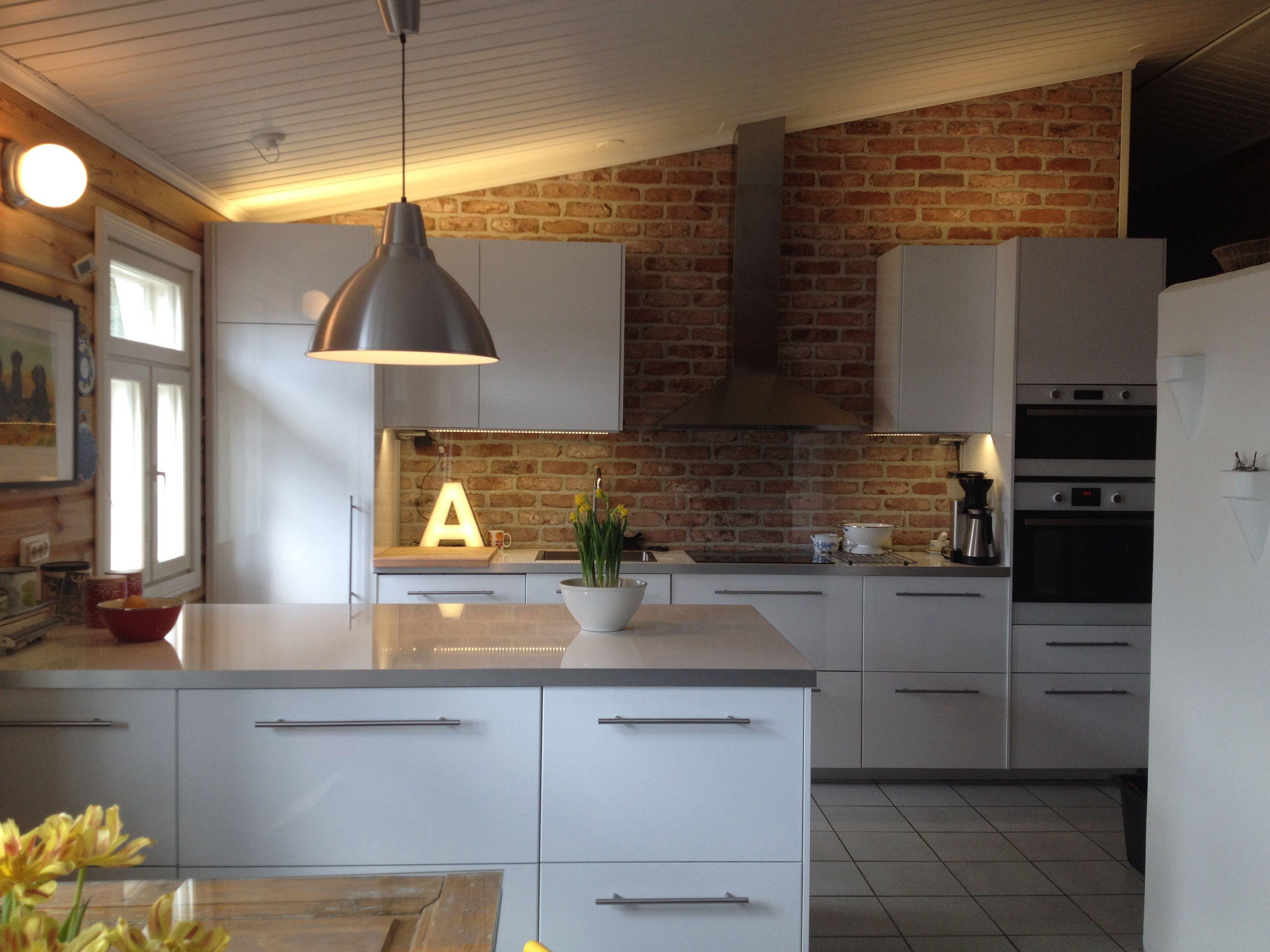 Tiiliseinä lisää luonnetta selkeälinjaisessa keittiössä. #etuovisisustus #keittiö