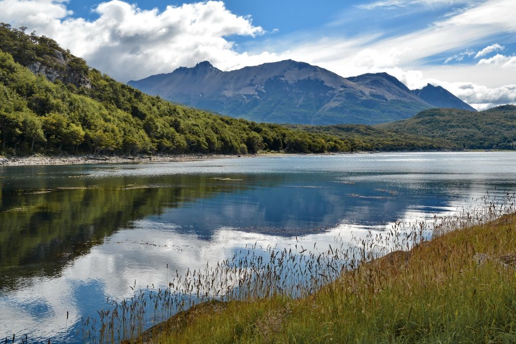 tierra del fuego national park, argentina. The park has dramatic scenery, with waterfalls, forests, mountains and glaciers. The Senda Costera (Coastal Path), connecting Ensenada Bay to Lapataia Bay on Lago Roca, is a popular hiking trail within the park. The park can be reached by car or by train.