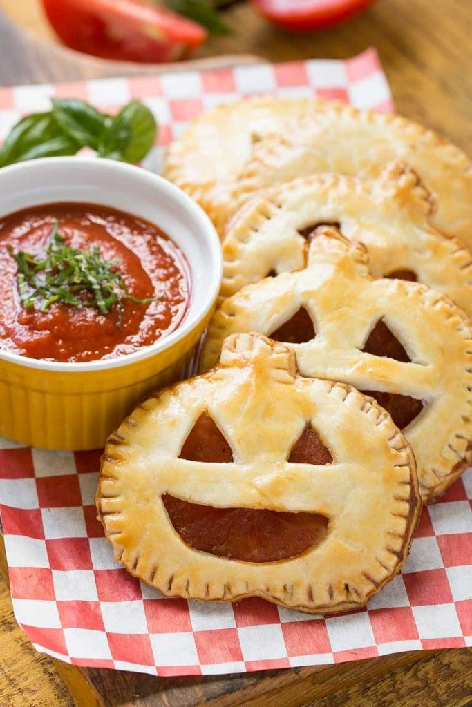 These homemade jack-o-lantern pepperoni pizza pockets are a fun - halloween food ideas for kids party
