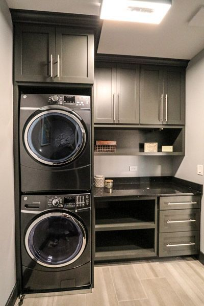 Second Floor Laundry Room With Custom Built And Grey Painted Cabinetry Surrounding Stacked Washer Dryer