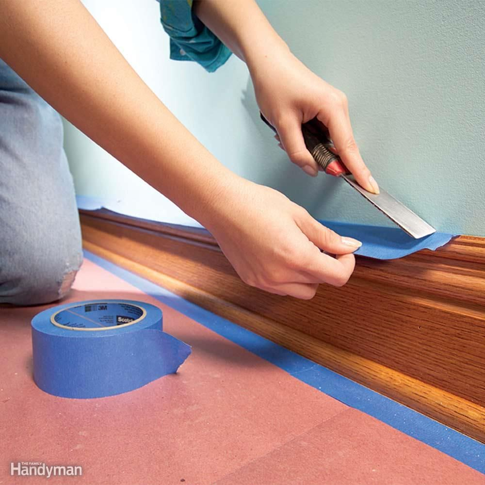 Don't waste time by completely covering baseboard with several strips of tape. A single overhanging strip of wide tape will catch roller splatters just as the roof overhang on your house keeps rain off the siding. Use 1-1/2-in. tape for narrow baseboard, 2-in. tape for wider baseboard. Tape won't stay stuck to dusty surfaces, so wipe down all your trim before masking. To minimize paint seepage under the tape, press the tape down hard by running a flexible putty knife over it.