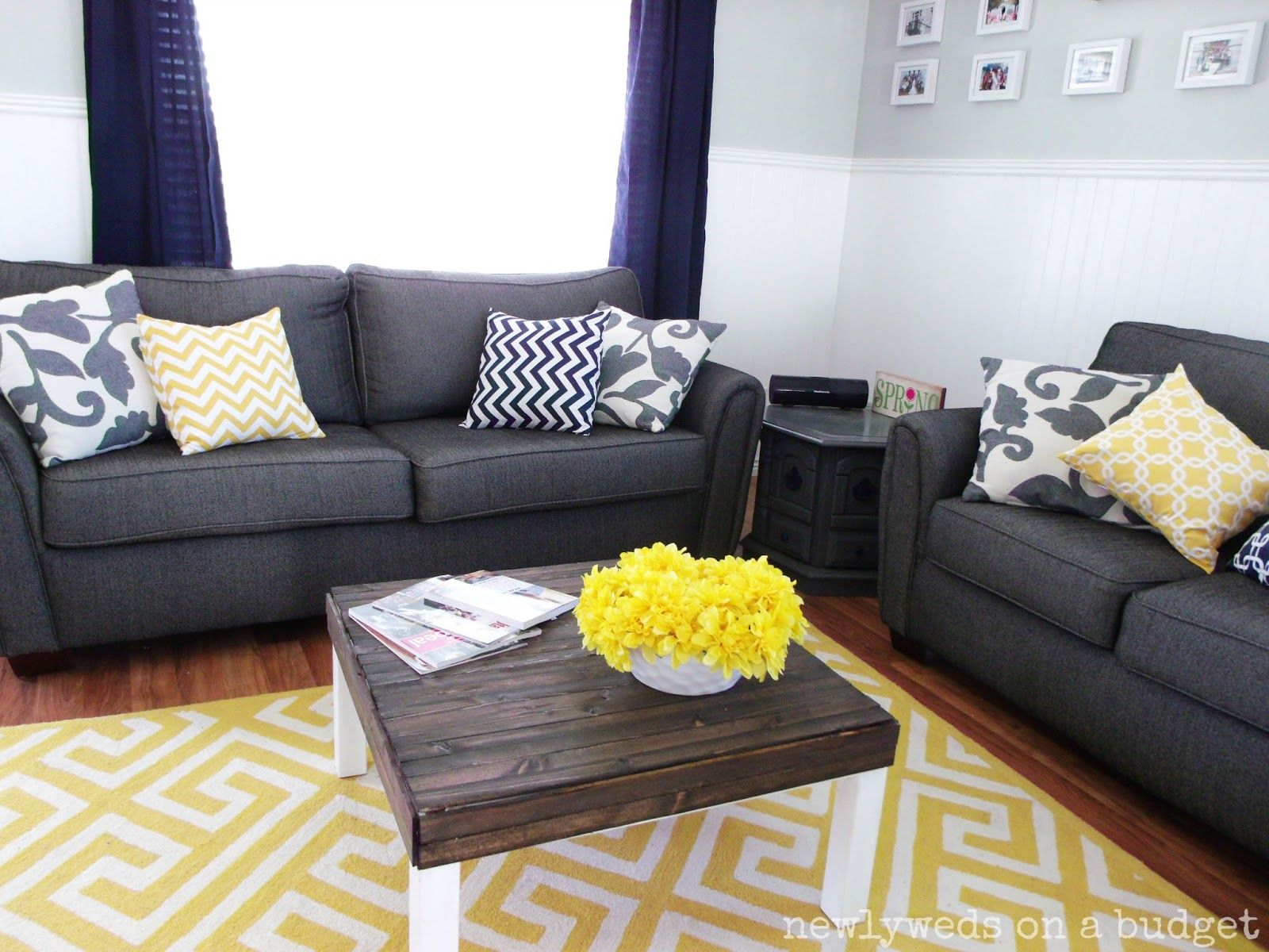 yellow and grey living room. white walls. bright yellow plant on
