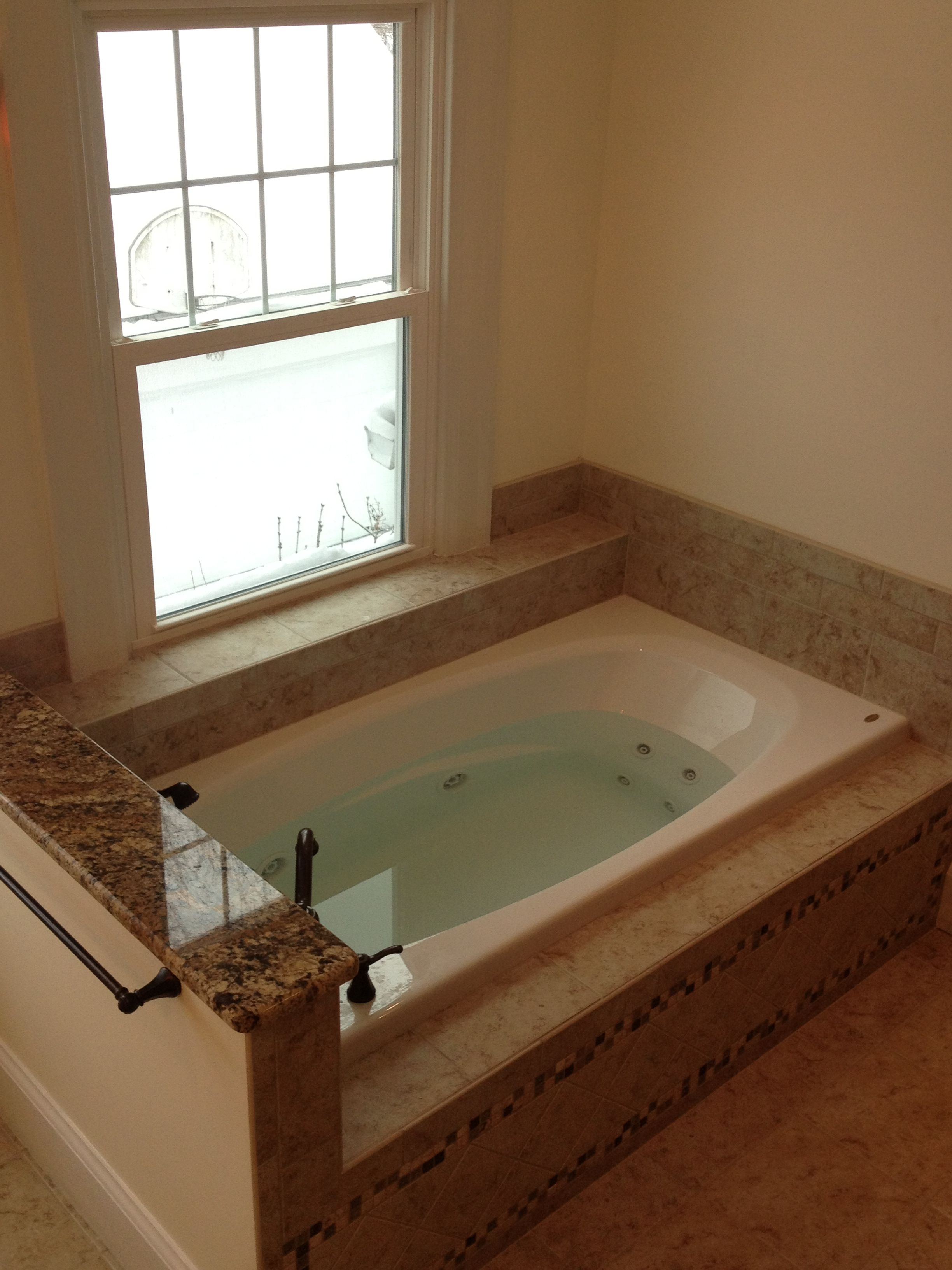 A drop-in tub with tile surround has visual separation from the ...