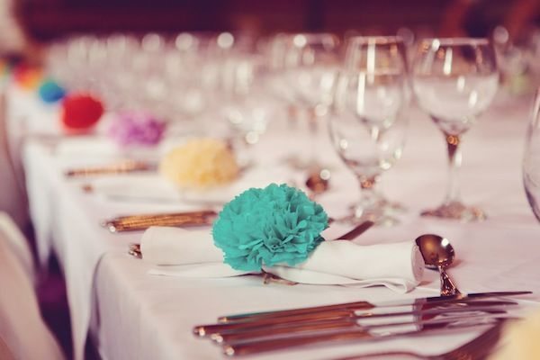 The best thing about wedding paper poms is that they can be used in a multitude of ways. One idea is tying them alongside the aisle pews or chairs at the wedding ceremony. Doing so can help incorporate the wedding theme's colors into the decor. Poms can be used at the reception by tying them onto napkin rings. Rather than using a plain napkin ring or simply folding the napkin, the poms can be integrated by attaching them to the ring
