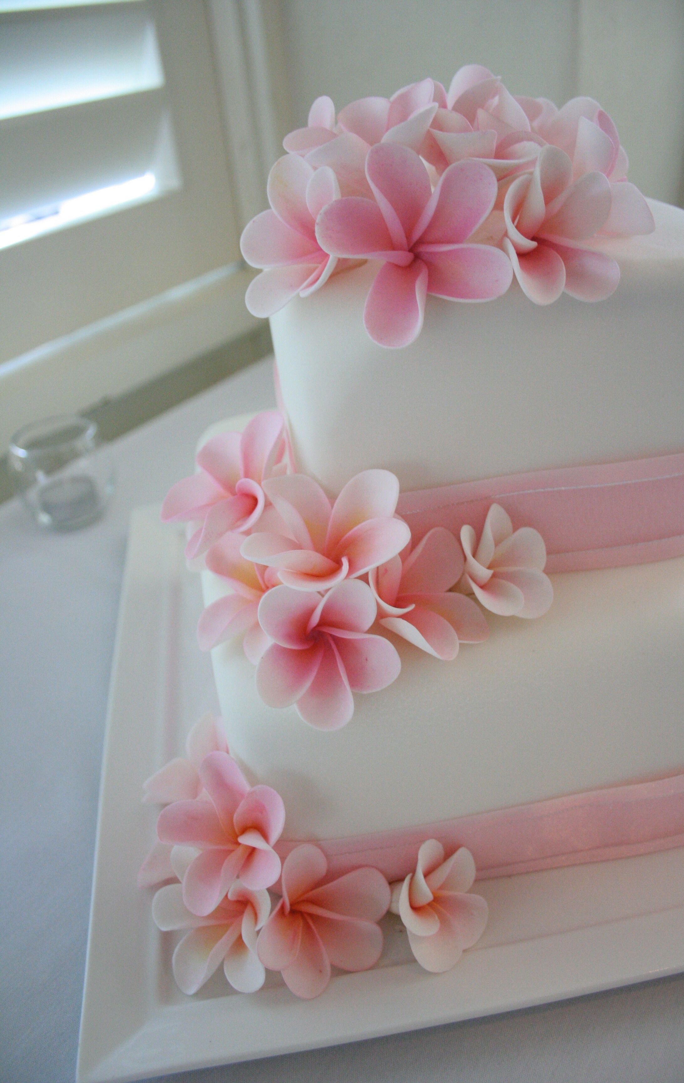 Two Tier Cake Covered In Fondant And Decorated With Sugar Flower