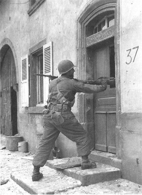 Rifleman of the 70th Division, 7th Army search for snipers