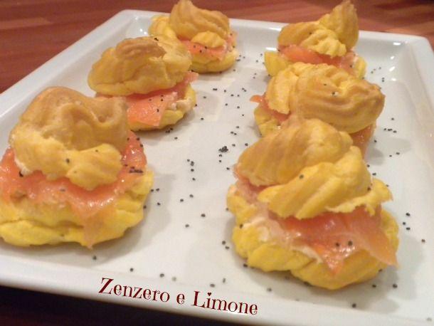 I bigné salati al salmone affumicato sono degli ottimi finger food da offrire durante le feste. Questi sono guarniti con semi di papavero