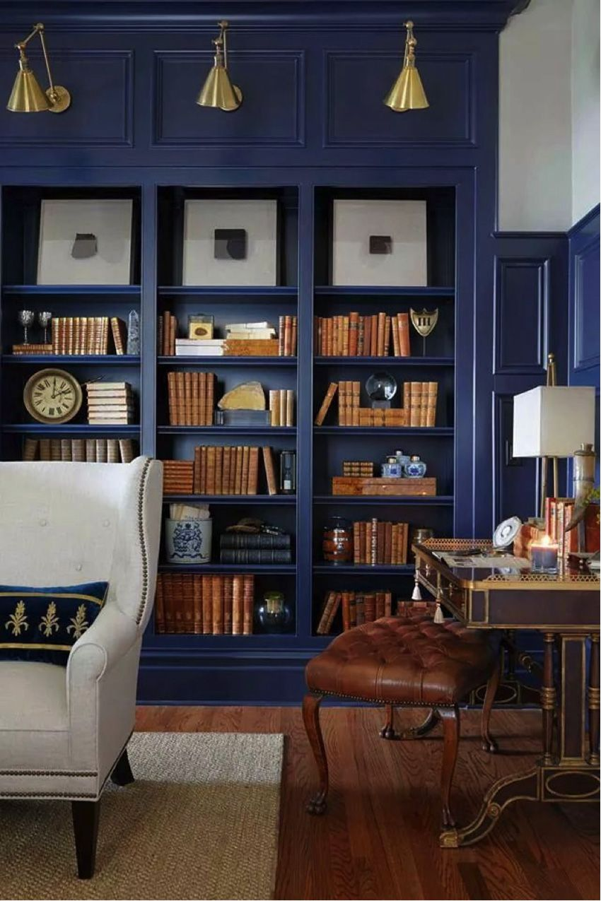 lighting a living room | alice lane home collection | navy bookshelves, styled bookshelves, linen wingback chair, antique desk, tufted ottoman