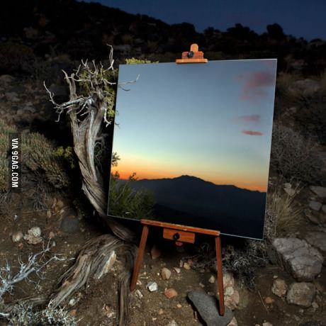 Photo of a mirror, on an easel in the desert, that looks like a painting