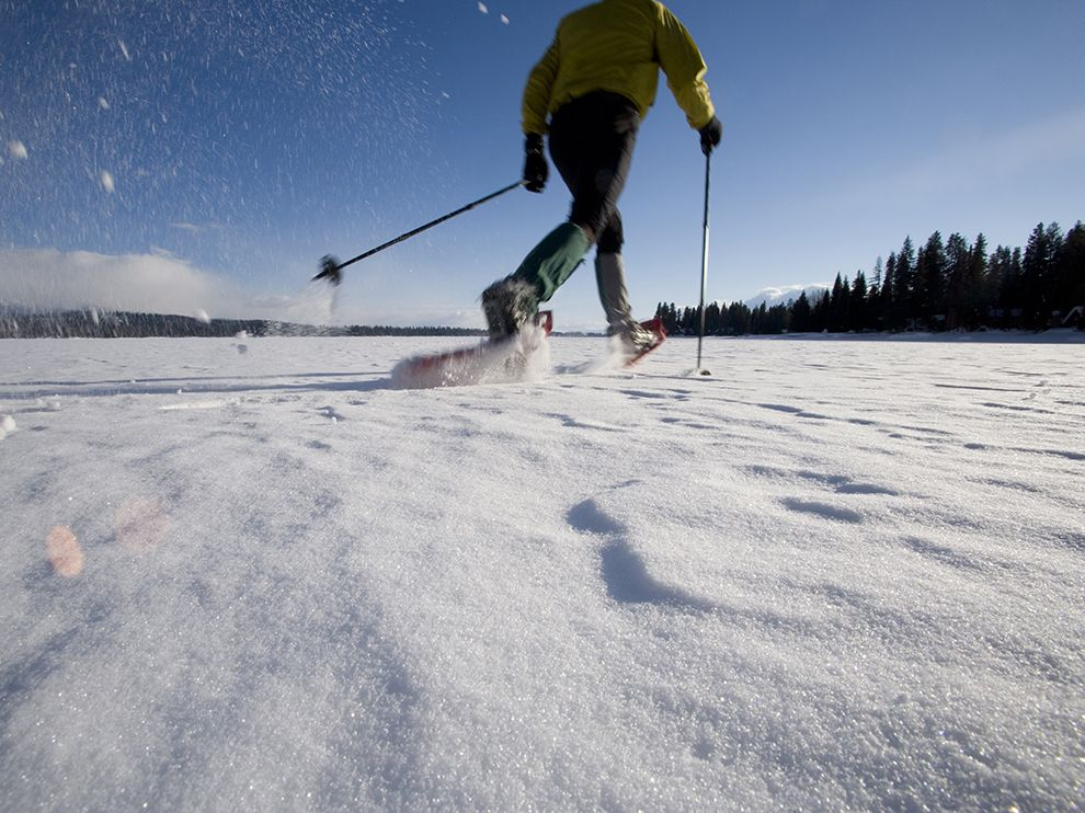 Picture of a man with snowshoes walking around a lake near McCall, Idaho