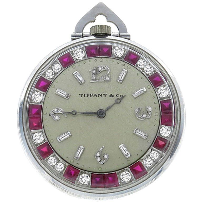 Rare Tiffany & Co. Diamond Ruby Platinum Pocket Watch - Made of platinum. this watch is set with bright red square cut rubies weighing approximately 3ct. and sparkling round cut diamonds that weigh approximately 3ct. graded F color with VS1 clarity. The watch measures 41.5mm in diameter, and weighs 51.1 grams. The back of the watch is encased with crystal showcasing the entire movement that is signed Tiffany & Co New York with numbers. The watch is in excellent condition, and comes with a…