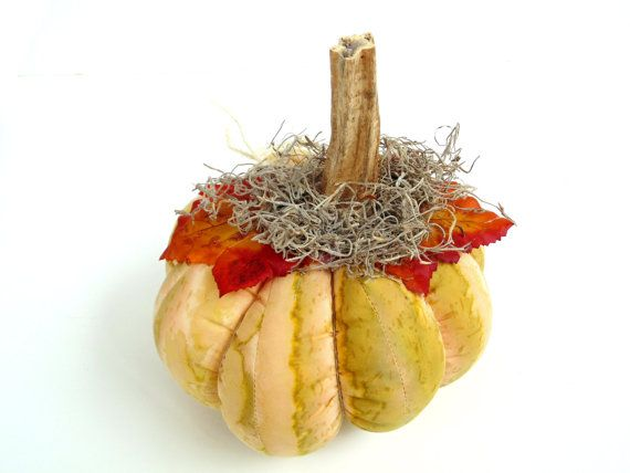 Fabric stuffed pumpkin is made of cotton batik fabric in colors of creamy beige, green and brown. It has faux leaves in bright orange and yellow, and a real pumpkin stem that is surrounded with Spanish moss. It has tendrils of jute string and is segmented with hemp string. It is stuffed full with non-allergenic fiber filling.  I saved many of my pumpkin stems from my garden last year to make these unique pumpkins. Add this festive stuffed pumpkin to your Fall and Thanksgiving decor. For…