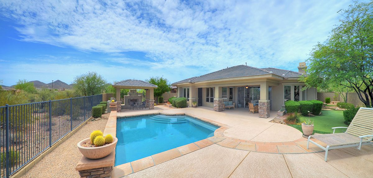 Savor magnificent mountain vista views from your spectacular yard. An entertainer's paradise, the yard has a heated pool with water feature and chiller, elevated deck with fire pit, putting green with sand trap and magnificent Ramada with fireplace and barbeque. View fencing overlooks natural Sonoran desert. Wow!  #backyard #outdoor #sparklingpool #mountainviews #ramada #firepit #puttinggreen #desert #waterfeature #relax #retreat #entertain #homeforsale #arizona #realestate