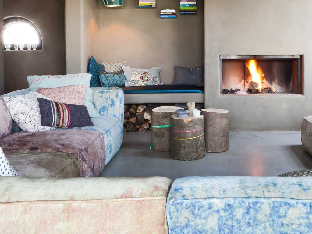 Bohemian living space - eclectic modular sofa, raw tree stump side tables, built in fire place and cosy day bed nook. Love it all!