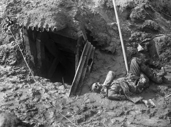 A rotting corpse of a German soldier lying outside the entrance of a destroyed bunker. Battle of the Somme, 1916.