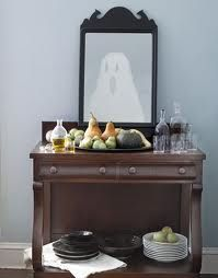 DIY Halloween window decoration.  See through cloth of wax paper cut to look like ghost and tAped to mirror