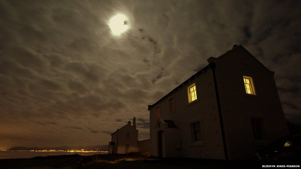 Clouds almost completely cover the night sky, expect for the moon. A house with its lights on is seen in the foreground, in the background some city lights can be seen across water