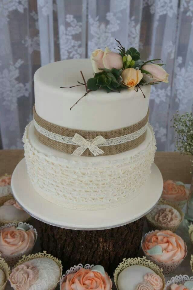 two tier rustic bridal shower cake with ruffles layers burlap and lace with a spray od peach and green florals sitting on a tree stump pedastal surrounded