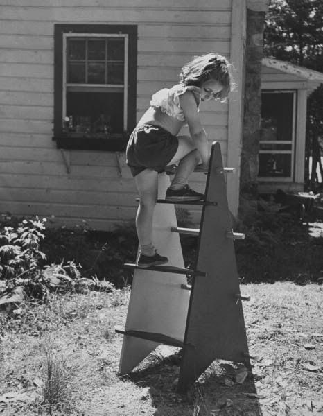Vintage photo of a little girl climbing. Nina Leen, 1953