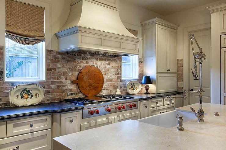 lovely kitchen boasts white cabinets paired with honed black countertops and a red brick. Black Bedroom Furniture Sets. Home Design Ideas