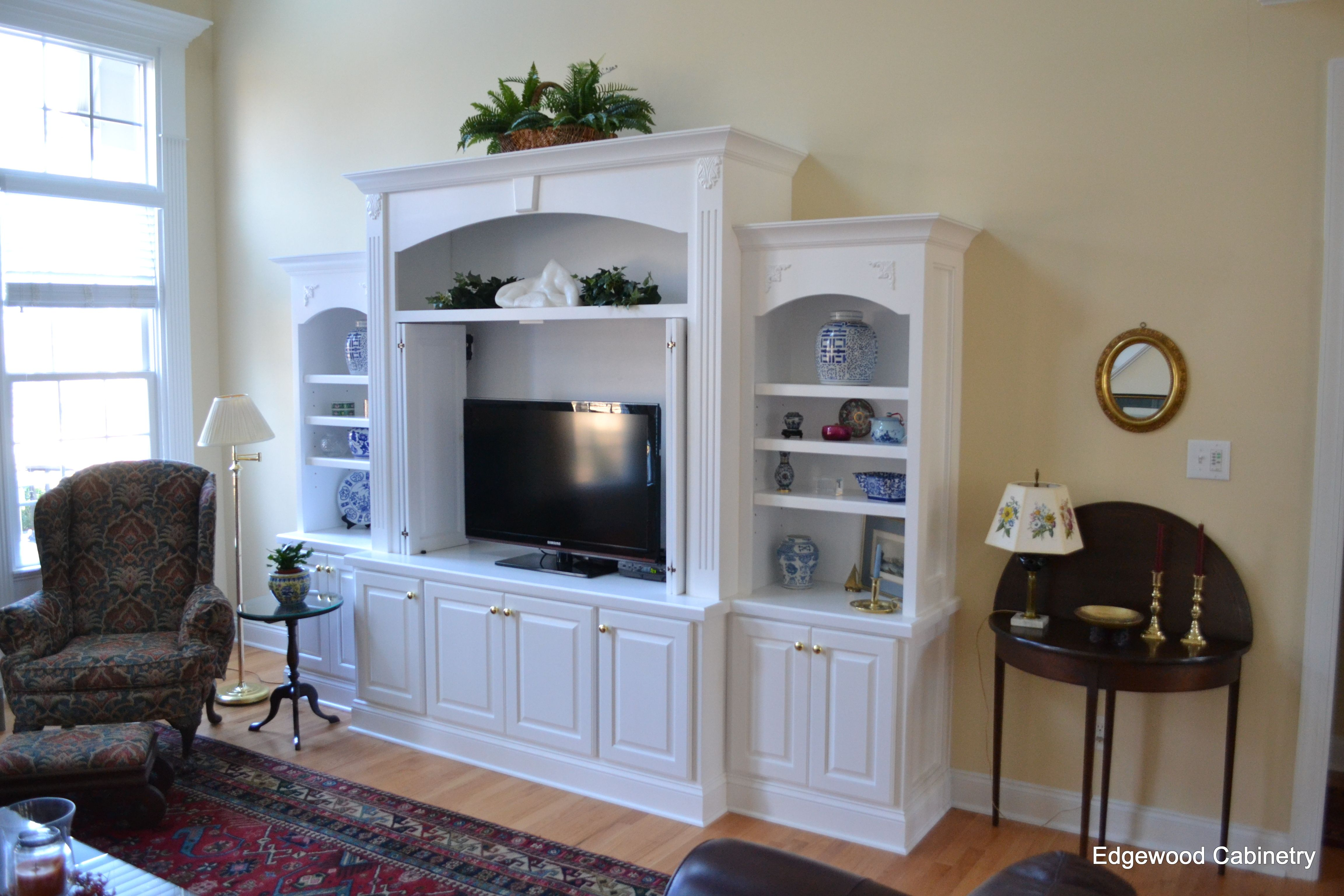 White entertainment unit with pocket doors to hide TV when ...